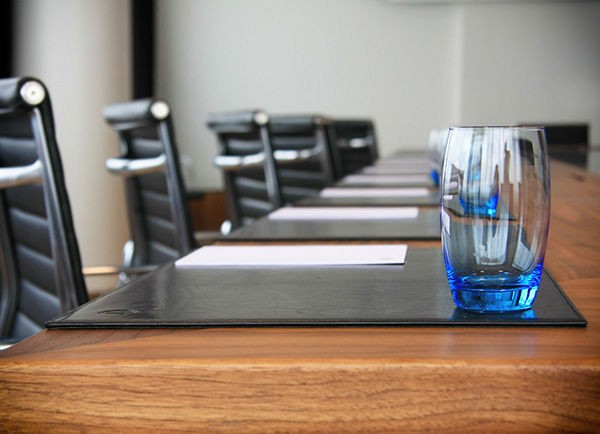 Photo of a board-room table with papers and empty glasses
