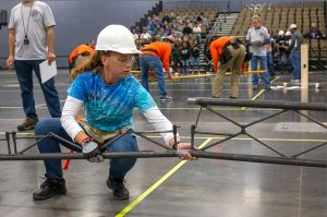 A member of the Florida Gulf Coast University steel bridge team works to assemble their bridge at the 2019 ASIC regional competition.